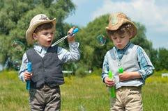 De identieke tweeling blaast zeepbels Stock Foto