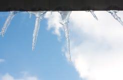 De ijskegels hangen van het dak Stock Foto