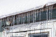 De ijskegels hangen van het dak van een oud huis met schil van pijn royalty-vrije stock afbeelding