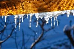 De ijskegels hangen van het dak en de smelting wanneer het weer verwarmt royalty-vrije stock foto
