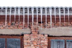 De ijskegels hangen van het dak van het oude huis, de recente winter of de Graaf Stock Foto's