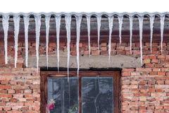 De ijskegels hangen van het dak van het oude huis, de recente winter of de Graaf Stock Foto