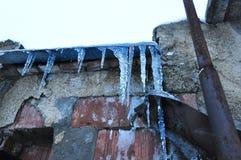 De ijskegels roofed het pleister van baksteenhuizen en roestige pijp Stock Afbeeldingen