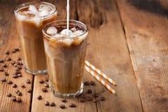 De ijskoffie in een lang glas met room goot over en koffiebonen op een oude rustieke houten lijst Koude de zomerdrank op een donk stock afbeelding