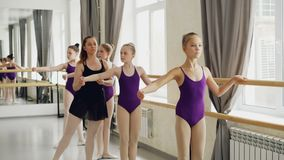 De ijverige jonge balletdansers doen plie en battementtendu terwijl hun vrouwelijke leraar verkeerd verbetert stock video
