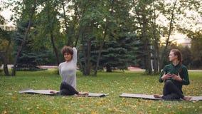 De ijverige yogastudent leert de positiezitting van het Koegezicht op mat en rekt wapens uit terwijl de ervaren leraar is stock videobeelden