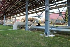 De ijzerbrug, de overgang met treden en traliewerk door grote dikke pijpen met stoom en gecondenseerd, een pijpleidingsviaduct stock foto's