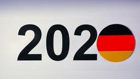 De illustratie, nieuw jaar, mannelijke hand zette op de lijst aangaande Duitse vlag, de bal van het land, 2020 stock videobeelden