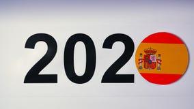 De illustratie, nieuw jaar, mannelijke hand zette op de lijst aangaande Spaanse vlag, de bal van het land, 2020 stock footage