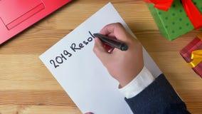 De illustratie, nieuw jaar, mannelijke handen schrijft in een notitieboekje, de resolutie van 2019 stock videobeelden
