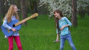 De imitatie pop musicusprestaties in de bospark Gelukkige kleine meisjes voor de gek houden rond het dansen en zingen liederen di stock video