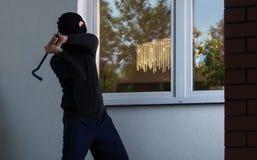 De inbreker probeert om een venster te breken Stock Afbeelding