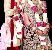 De Indische bruid en de bruidegom stellen voor mooie portretten na hun kleurrijke jaimalaceremonie stock foto