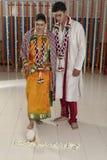 De Indische Hindoese Bruid die het huis van de bruidegom na huwelijk ingaan door pot te duwen vulde met rijst met haar voet. Royalty-vrije Stock Afbeeldingen