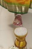 De Indische Hindoese Bruid die het huis van de bruidegom na huwelijk ingaan door pot te duwen vulde met rijst met haar voet. Royalty-vrije Stock Afbeelding