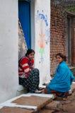 De Indische jonge vrouwen zitten en babbelen op een huisportiek stock afbeelding