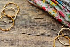 De Indische juwelenarmbanden en de bloemen etnische stof liggen op een houten achtergrond royalty-vrije stock foto