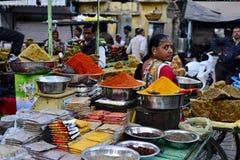 De Indische vrouw verkoopt kleurrijke kruiden op de straatmarkt stock afbeelding