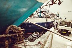 De Indonesische havenarbeiders maken een schip met een bloem leeg binnen in zakken doet lading Stock Foto