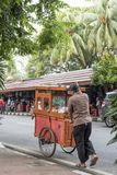 De Indonesische mens duwt een voedselkar bij de de antiquiteit en vlo van Jalan Surabaya stock fotografie