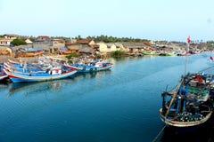 De Indonesische vissersboten van het rivierdok en communautaire huisvesting stock afbeelding