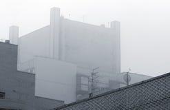 De industriële bouw in mist Stock Afbeeldingen