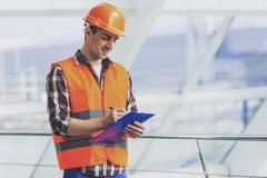 De industriële Ingenieur in Gele Helm maakt Nota's stock afbeeldingen