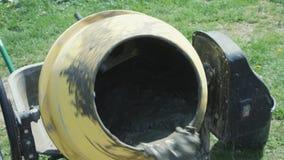 De industriële machine van de cementmixer bij bouwwerf Het concrete gieten Bouwvakker die mortier mengen pouring stock footage