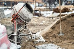 De industriële machine van de cementmixer bij huisbouwwerf Concrete mixer, zand en hulpmiddelen royalty-vrije stock foto