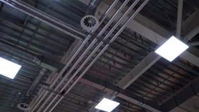 De de industriële pijpen en lampen van het hvacsysteem op plafond van groot winkelcentrum stock footage