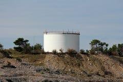 De industriële tank van de witte olieraffinaderij met beschermende die omheining bovenop kleine die heuvel wordt geplaatst met ro stock afbeeldingen
