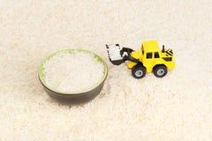 De industriële tractorstuk speelgoed korrels van de ladingsrijst aan plaat Stock Fotografie