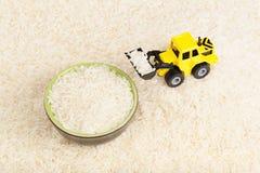 De industriële tractorstuk speelgoed zaden van de ladingsrijst aan plaat Royalty-vrije Stock Foto