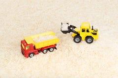 De industriële tractorstuk speelgoed zaden van de ladingsrijst aan stortplaatsvrachtwagen Stock Afbeeldingen