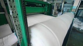 De industriële transportband rolt synthetische stof in een spoel stock videobeelden
