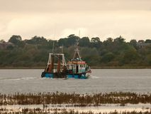 De industrie vissersboot die langs de rivier donkere herfst reizen Stock Fotografie