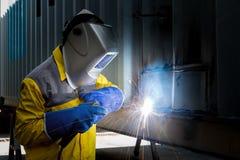 De industriearbeider met lassenstaal aan de structuur van de reparatiecontainer Stock Afbeelding