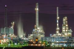 De industrieinstallatie van de olieraffinaderij met het bootparkeren dichtbij rivieroever Royalty-vrije Stock Afbeeldingen
