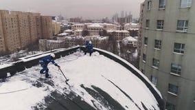 De industriella klättrarna gör klar ett tak från den ackumulerade insnöade Moskva _ lager videofilmer