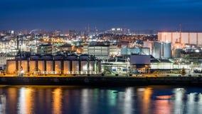 De industriezone van Hamburg bij nacht met bezinningen over het water stock foto's