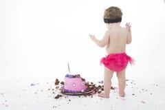 De ineenstortingsspruit van de cake: Het meisje van de baby en grote slordige cake! stock afbeelding