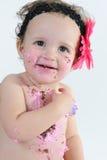 De ineenstortingsspruit van de cake: Slordig babymeisje na het eten van verjaardagscake! stock afbeelding