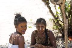 De infödda flickorna dekorerar deras framsidor, Amoronia den orange kusten, Madagascar Arkivbild