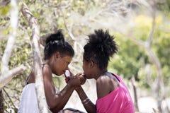 De infödda flickorna dekorerar deras framsidor, Amoronia den orange kusten, Madagascar Royaltyfri Bild