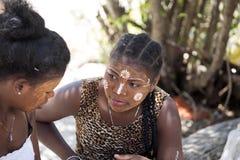 De infödda flickorna dekorerar deras framsidor, Amoronia den orange kusten, Madagascar Arkivfoto