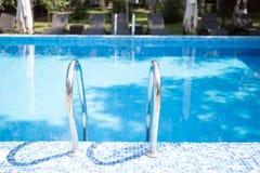 De ingang aan het openlucht zwembad leeg zwembad met ladder stock afbeelding