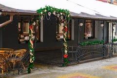 De ingang aan de koffie is verfraaid met takken van sparren en Kerstboomdecoratie in de winter op de straat royalty-vrije stock afbeeldingen