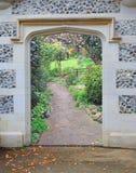 De ingang van de de gatewaydeur van de steenboog aan mooie tuin bloeit installaties stock foto's