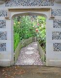 De ingang van de de gatewaydeur van de steenboog aan mooie tuin bloeit installaties royalty-vrije stock fotografie