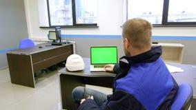 De ingenieur bekijkt het groene scherm en het spreken op walkie-talkie binnen de controlekamer stock footage